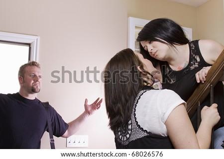 Husband Coming Home Finding His Wife Cheating with another Woman - stock photo