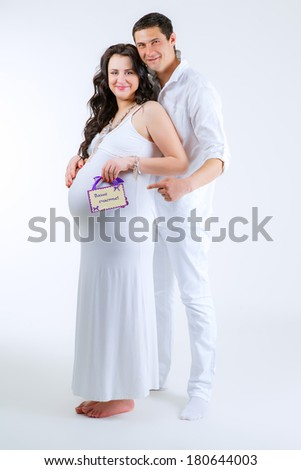 husband embracing his pregnant wife - stock photo