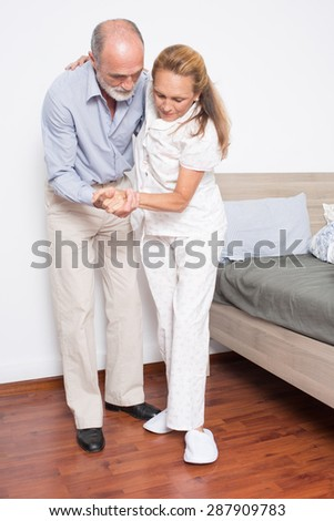 Husband helps wife to get out of bed - stock photo