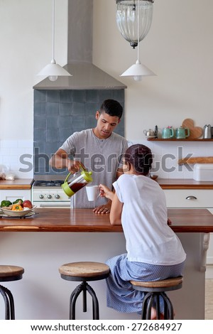 husband is pouring coffee for his wife in kitchen early morning breakfast routine - stock photo