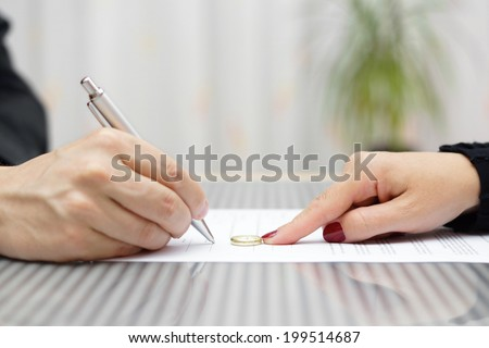 husband signing divorce agreement and woman push away weeding ring - stock photo