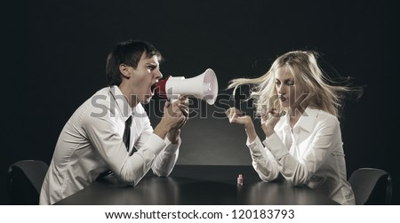 Husband using a megaphone to scream at his wife applying nail polish - stock photo