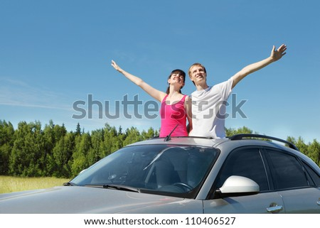 Husband, wife arrange hands in hatch of car in field - stock photo