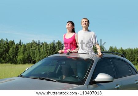 Husband, wife stand in hatch of car in field - stock photo
