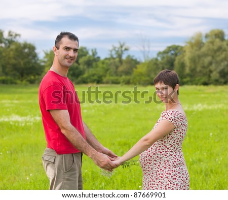 Husband with his pregnant wife on the green meadows - stock photo