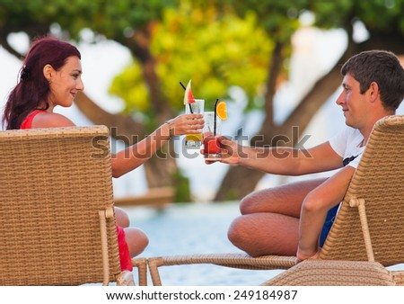 husband with his wife lying at sunbed near pool, honeymoon on the beach - stock photo