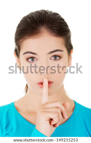 Hush be quiet woman isolated. Teen girl with finger on her lips. - stock photo