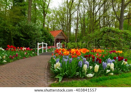 hut in the spring  garden with stone path and blooming flowers, Keukenhof, Netherlands - stock photo