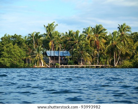 Hut on tropical coast with dock and coconut trees, Caribbean, Panama - stock photo