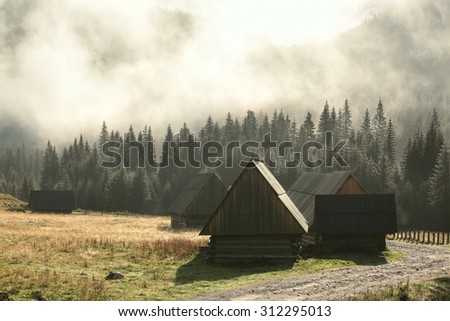 Huts along the trail in the Tatra Mountains on a foggy morning. - stock photo
