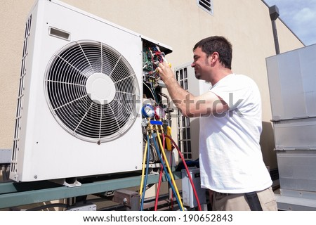 HVAC technician working on a mini-split condensing unit - stock photo