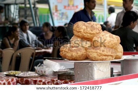 HYDERABAD,AP,INDIA-JANUARY 12:Indian Popular Snack Puri on display in a public space on January 12,2014 in Hyderabad,Ap,India.Made out of wheat / maida flour,fried in oil a common food variety. - stock photo