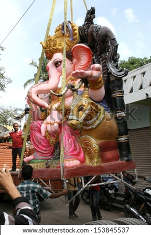 HYDERABAD,AP,INDIA- SEPTEMBER 1:People transport Ganesha idol for Hindu festival ganesha chathurthi September 1,2013 in Hyderabad,India.Devotees perform 10 day puja in Thousands of neighbourhoods. - stock photo