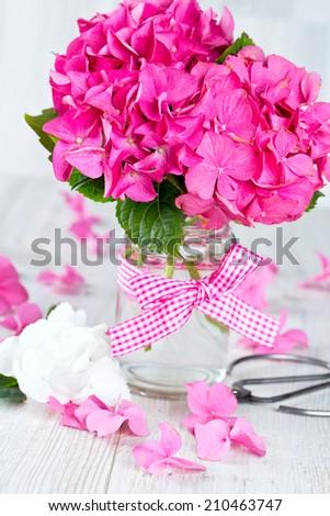 hydrangea flower in vase on wooden surface - stock photo