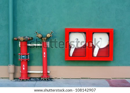 Hydrant with water hoses and fire extinguish equipment - stock photo