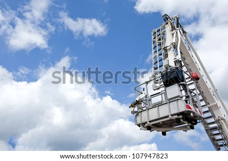 Hydraulic aerial fire platform on the sky background. - stock photo