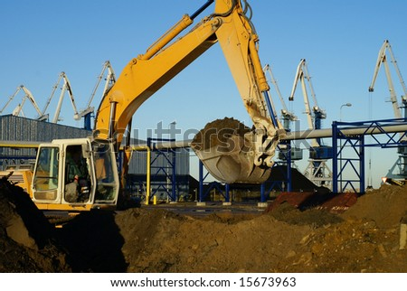 Hydraulic excavator at work. Shovel bucket and cranes against blue sky - stock photo