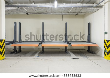 Hydraulic lifts for the car in the underground parking. - stock photo