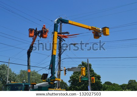 Hydro workers on a lift truck repairing hydro lines in Hamilton Ontario, under blue sky. - stock photo