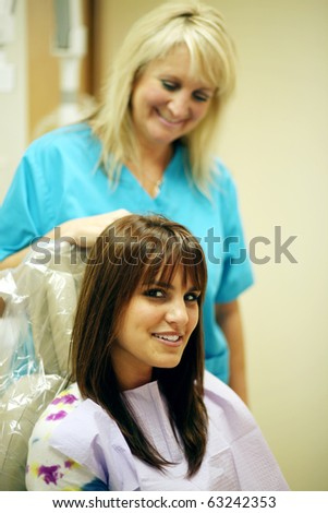 hygenist with patient in office with focus on patient - stock photo