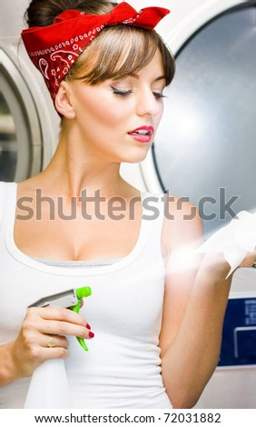 Hygiene And Cleanliness Is In The Air As A Beautiful Lady Spraying A Mist Of Cleaning Liquid Onto A Cloth From A Spray Bottle In A House Work Cleaning Image - stock photo