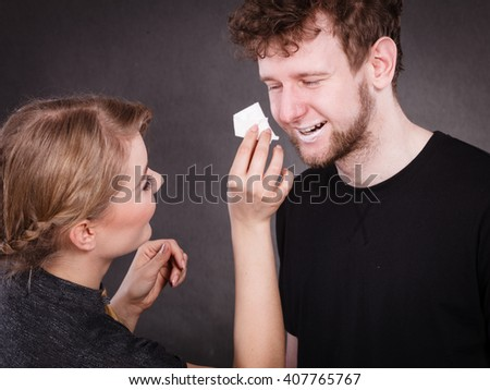 Hygiene and skincare concept. Protection and help in relationship. Smiling happy woman wipe cream face nose of funny man by hygienic tissue. Girlfriend takes care of her boyfriend. - stock photo