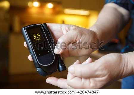 Hypoglycemic diabetic patient testing her blood for sugar level at home; low blood sugar. Medical process, self-diagnose, common metabolic, widespread and modern epidemic disease concept.   