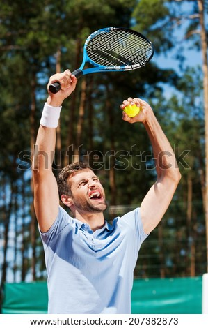 I am a winner! Happy young man in polo shirt raising his tennis racket up while standing on tennis court  - stock photo