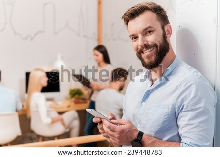 I am always in touch. Confident young beard man holding mobile phone and smiling while his colleagues working in the background - stock photo