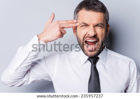 I am fed up with it! Furious mature man in shirt and tie gesturing handgun near head and shouting while standing against grey background - stock photo