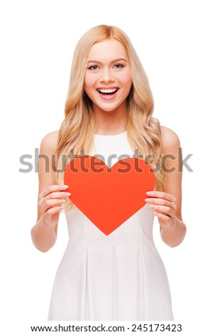I am in love! Beautiful young blond hair woman holding big heart shaped paper and smiling to you while standing isolated on white background - stock photo