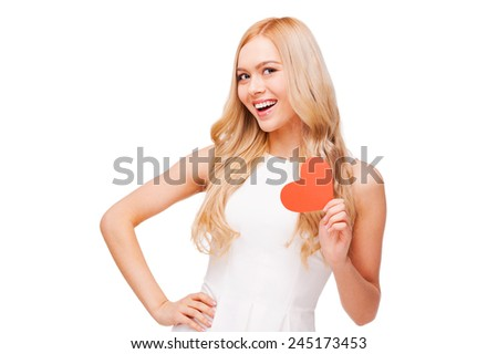 I am in love! Beautiful young blond hair woman holding heart shaped valentine card and smiling while standing isolated on white - stock photo
