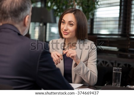 I am ready to sign a contract with you. Attractive young businesswoman is discussing project with her client. She is sitting and holding a pen. The woman is smiling - stock photo