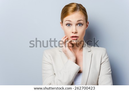 I am so scared. Terrified young businesswoman holding hand on her cheek while standing against grey background - stock photo