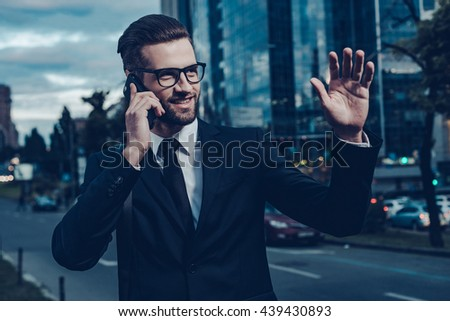 I can already see you! Night time image of confident young man in full suit talking on the mobile phone and waving to someone while standing outdoors with cityscape in the background - stock photo