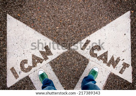 I can and can't dilemma concept with man legs from above standing on signs - stock photo