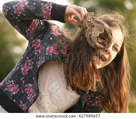 I Can See You. A young girl is using a piece of wood missing a knot to play a game of pretend. She is pretending the wood is magic and through the hole she can see all kinds of magic creatures.  - stock photo