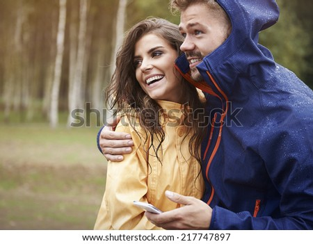 I checked the weather on mobile phone, it shouldn't rain - stock photo