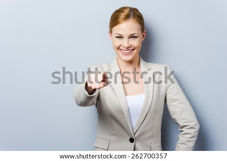 I choose you! Beautiful young businesswoman pointing you while standing against grey background - stock photo
