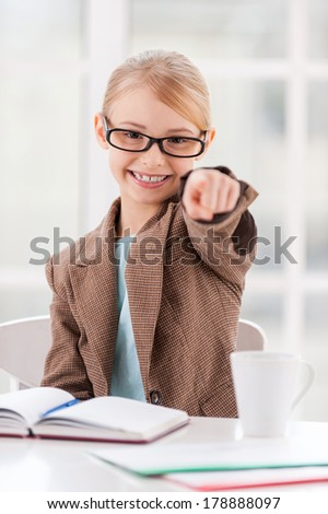 I choose you! Cheerful little girl in glasses and formalwear sitting at the table and pointing you  - stock photo