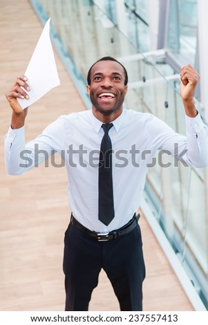 I did it! Top view of happy young African man in shirt and tie holding paper and keeping arms raised  - stock photo