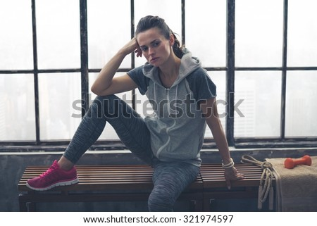 I didn't make my goal. Next time. Next time, I'll beat it - I won't just meet it, I'll do even better. Here, a woman in workout gear is sitting on a loft gym bench, resting, looking frustrated. - stock photo