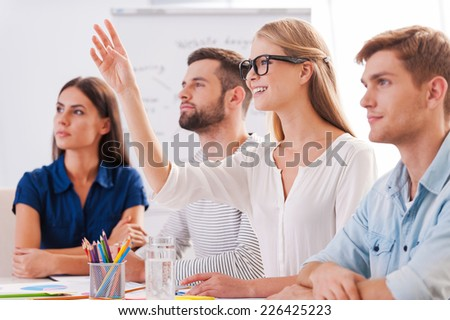 I have a question! Group of business people in smart casual wear sitting together at the table and looking away while beautiful woman raising her hand up and smiling - stock photo