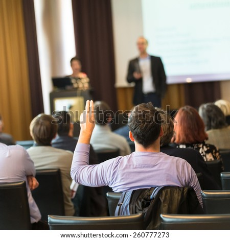 I have a question. Group of business people sitting at the chairs in conference hall. Businessman raising his arm. Conference and Presentation. Business and Entrepreneurship. - stock photo