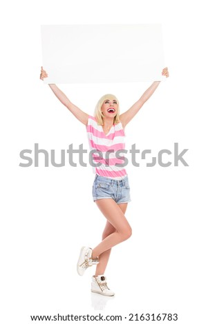 I have blank banner for you. Laughing blond woman standing on one leg and holding a blank placard over her head and reading. Full length studio shot isolated on white. - stock photo