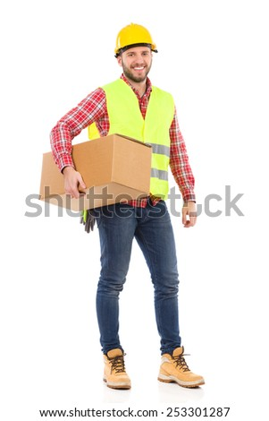 I have new tools. Smiling construction worker in yellow helmet and lime waistcoat standing with carton box under his arm. Full length studio shot isolated on white. - stock photo