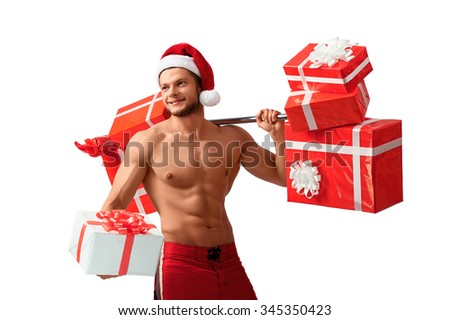I hear Christmas carols. Horizontal portrait of a shirtless Santa Claus with abs looking away cheerfully with a gift in his hand and a barbell on his shoulder - stock photo
