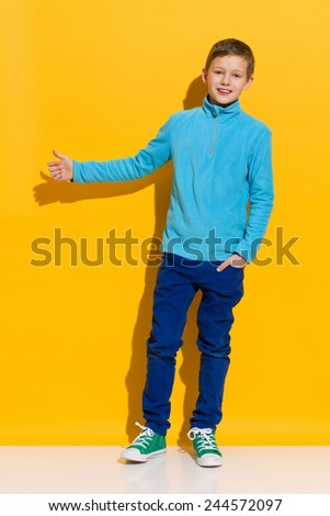 I like it. Young boy standing and showing thumb up. Full length length studio shot on yellow background. - stock photo