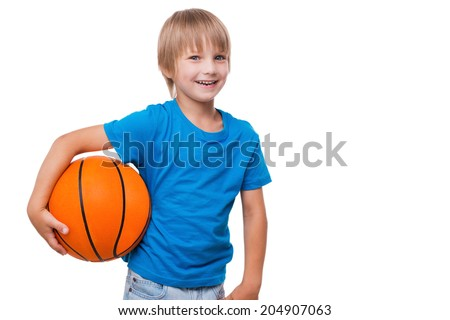 I love basketball! Cheerful little boy holding basketball ball and smiling while standing isolated on white - stock photo