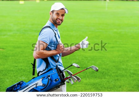 I love golfing! Rear view of young happy golfer carrying golf bag with drivers and looking over shoulder while standing on golf course - stock photo